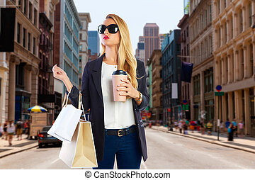Blond girl shopaholic in Manhattan Soho New York shopping...
