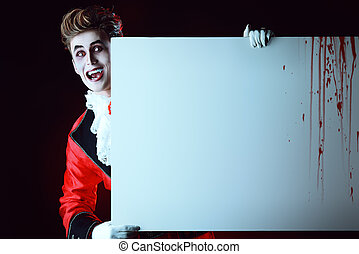 halloween - Bewitching handsome male vampire holding a...