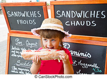 young girl eating a big sandwich