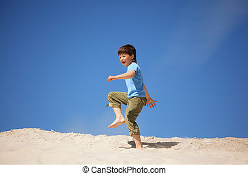 boy marching on beach