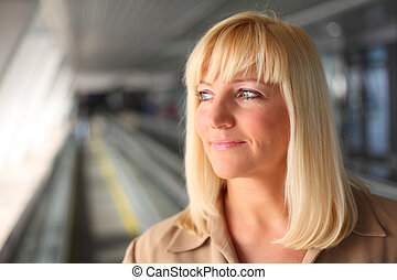 Pretty middleaged blonde on travelator