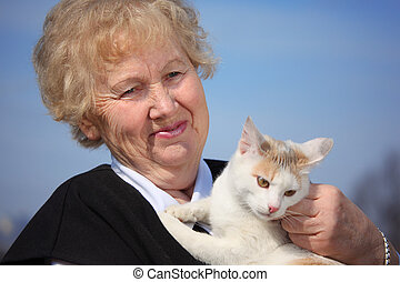 Portrait of aged woman with cat on sky