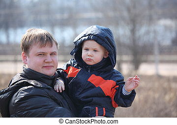 Father holds child on hands outdoor