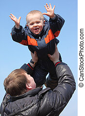 Child in sky on father\'s hands