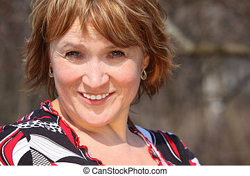 Smiling middleaged woman outdoor closeup