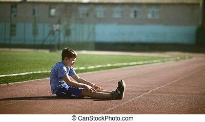 Teenage boy engaged in sport stadium stretching exercises...