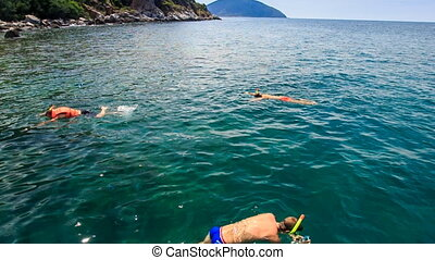 people swim in transparent azure sea at tourist boat and...