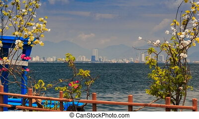 view of distant resort city across sea through blossom branches