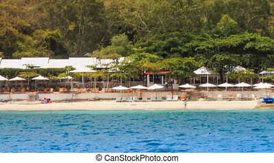 closeup village resort sand beach with umbrellas on island