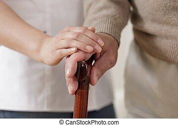 Carer holding old man hand - Close up of carer holding old...