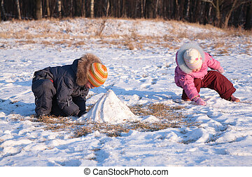 Children play in wood in winter