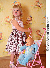 little girl with doll in carriage