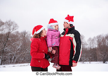 Parents with child on hands in park in winter