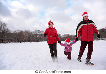 Parents with child run in park in winter