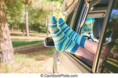 Female legs with socks resting over open window car -...