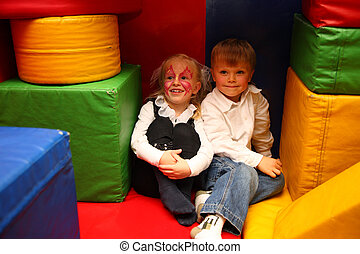 painted girl and boy sit in kindergarten