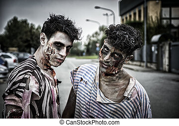 Two male zombies standing in empty city street looking at...