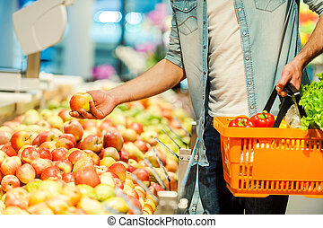 This should be fine. Close-up of young man holding apple and shopping bag while standing in a food store