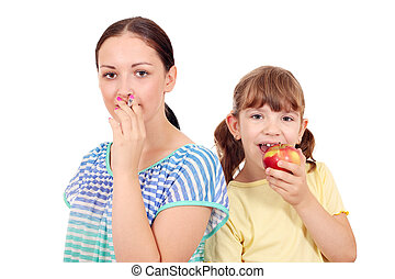 Girl smoking a cigarette and a little girl eating an apple...