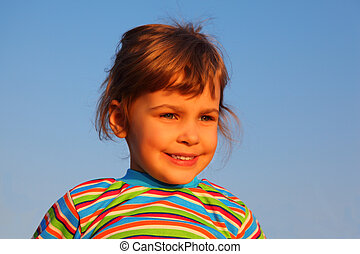 Little girl in striped t-shirt on sky background