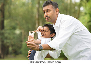 indian father and son playing slingshot at the park