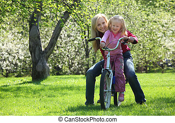 girl with mother sit on  bicycle in  blossoming spring garden