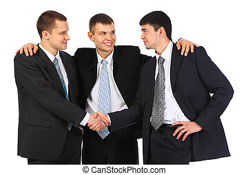 businessman observes hand shake of two others