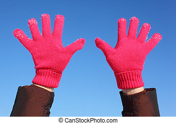 Two hands in red gloves against  blue sky
