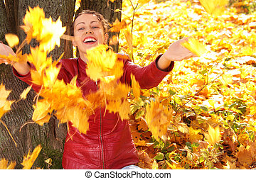 girl throws yellow maple leaves