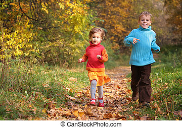 Two children run on wood autumn footpath