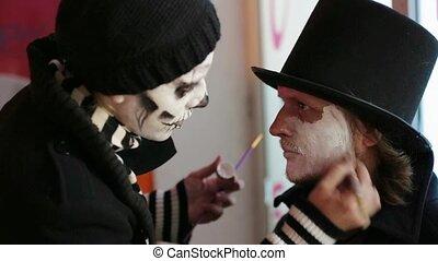 Young Woman Applying Makeup Onto Man's Face At Halloween
