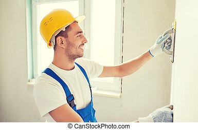 smiling builder with grinding tool indoors - business,...
