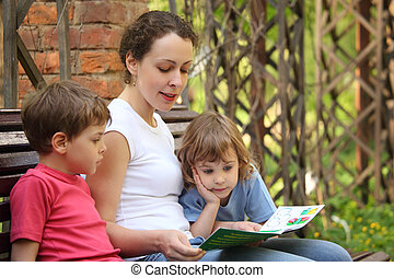 Mother reads book for children sits on bench