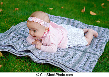 Happy little girl lying on a blanket in the park