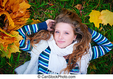 woman lying on the grass in autumn park