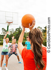 group of happy teenagers playing basketball - summer...