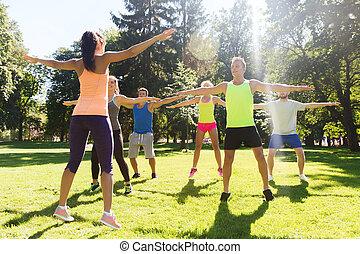grupo, de, feliz, amigos, ejercitar, Aire libre,