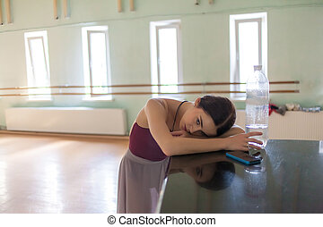 weary classic ballet dancer in rehearsal room background -...