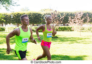 happy sportsmen couple racing wit badge numbers - fitness,...