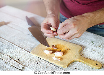 Man peeling garlic - Unrecognizable man in the kitchen...