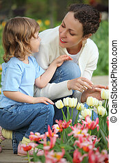 little girl together with mother sits at bed with tulips