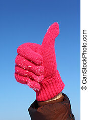 Hands in red glove against  blue sky shows gesture ok