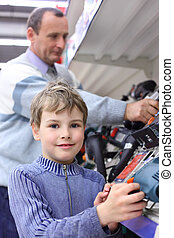 boy with elderly man in shop of electrotools