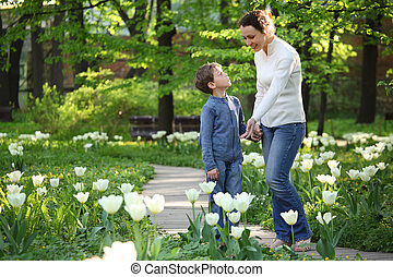 Mother shows to son blossoming white tulips in  garden