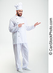 Happy chef cook holding copyspace on the palm - Full length...