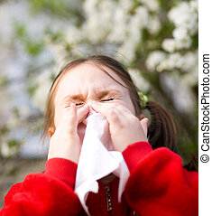 Portrait of a little girl is blowing her nose