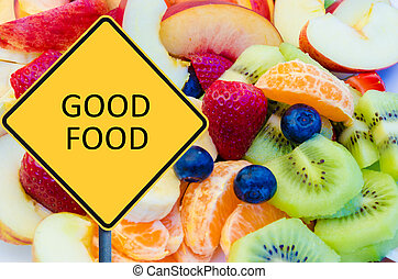Yellow roadsign with message GOOD FOOD over background of...