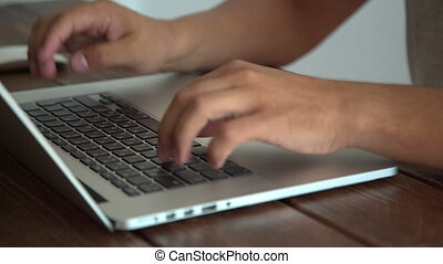 Man working with laptop placed on wooden desk - Man working...