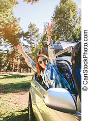 Happy woman raising arms through the window car - Portrait...