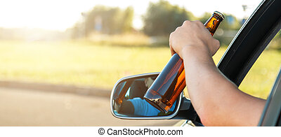 Car driver holding a bottle of beer - Car driver is holding...